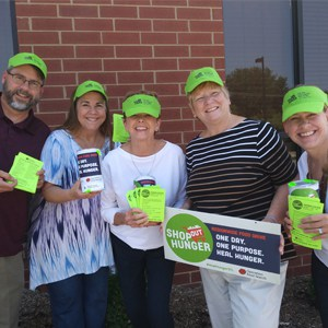 Five food pantry volunteers pose with their lime green hats and promo brochures and signs