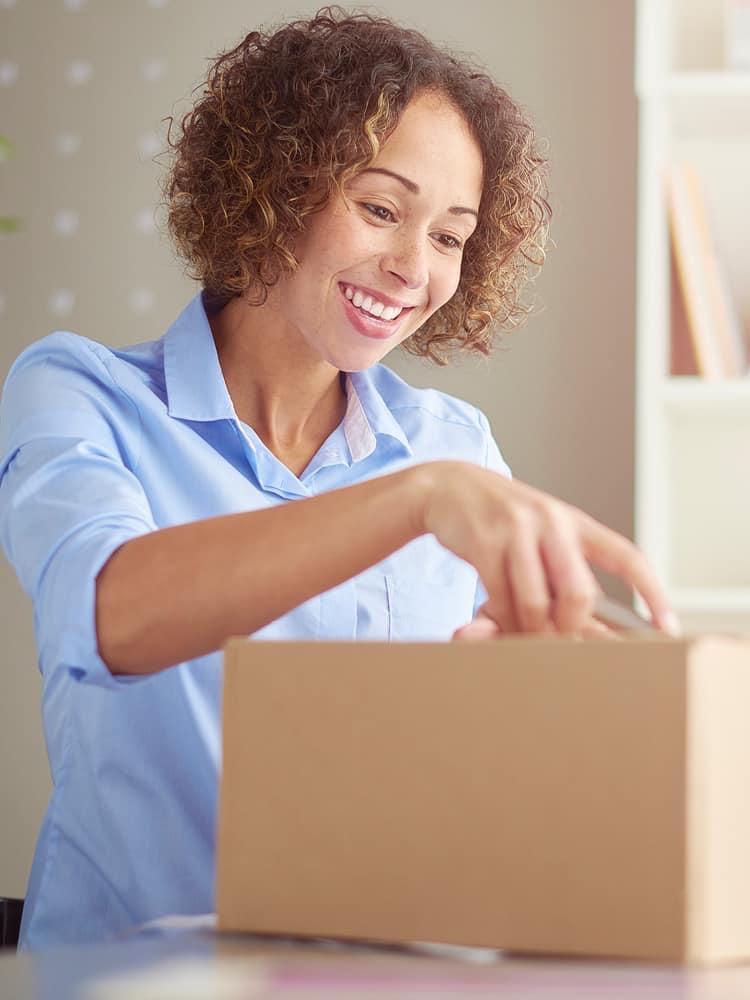 A woman opens a box.