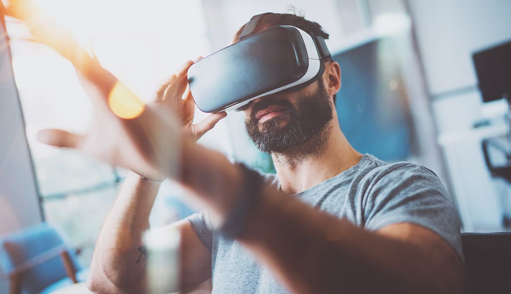 picture of man looking through virtual reality glasses. Businesses should thing of tech giveaways, like VR glasses, that people would want!