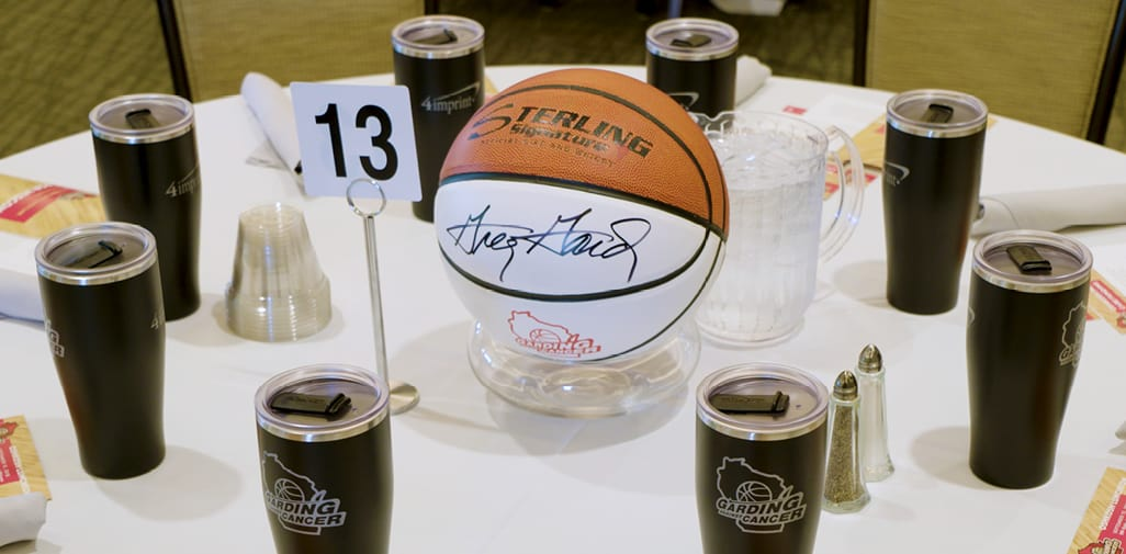 table at basketball themed fundraising event with nonprofit giveaways of logo mugs at each place setting