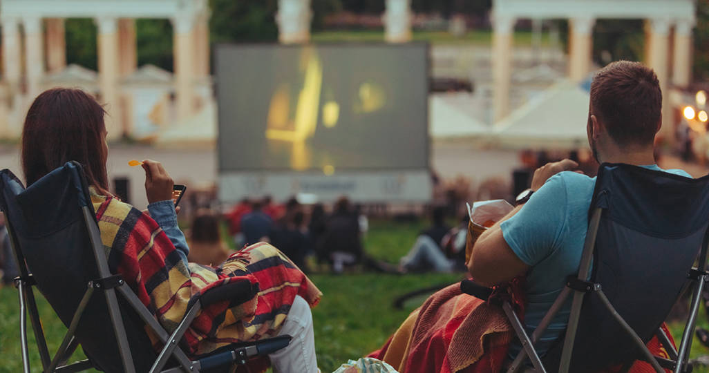 a man and woman sitting on lawn chairs with promotional blankets on their laps while watching an outdoor movie