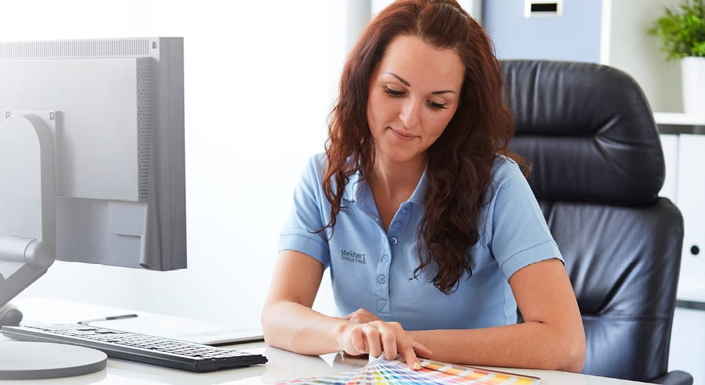 Woman sitting at desk wearing her business' custom work uniforms