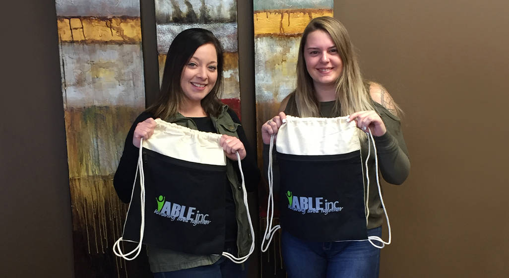 two employees holding up promotional bag - gifts for new employees - 4imprint