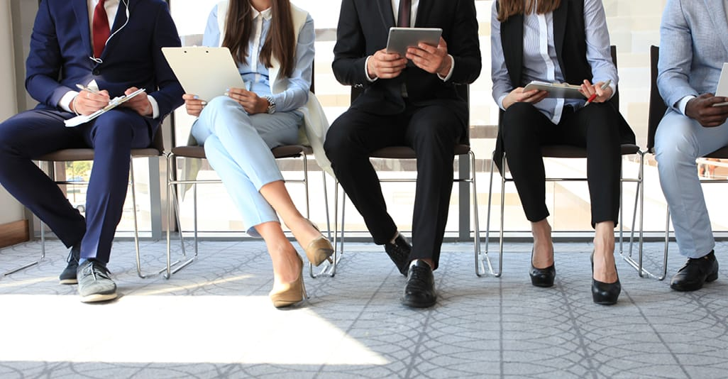 Photo showing a line of people sitting in chairs waiting for a job interview. Companies should think about employee recruitment giveaways as part of the hiring process.