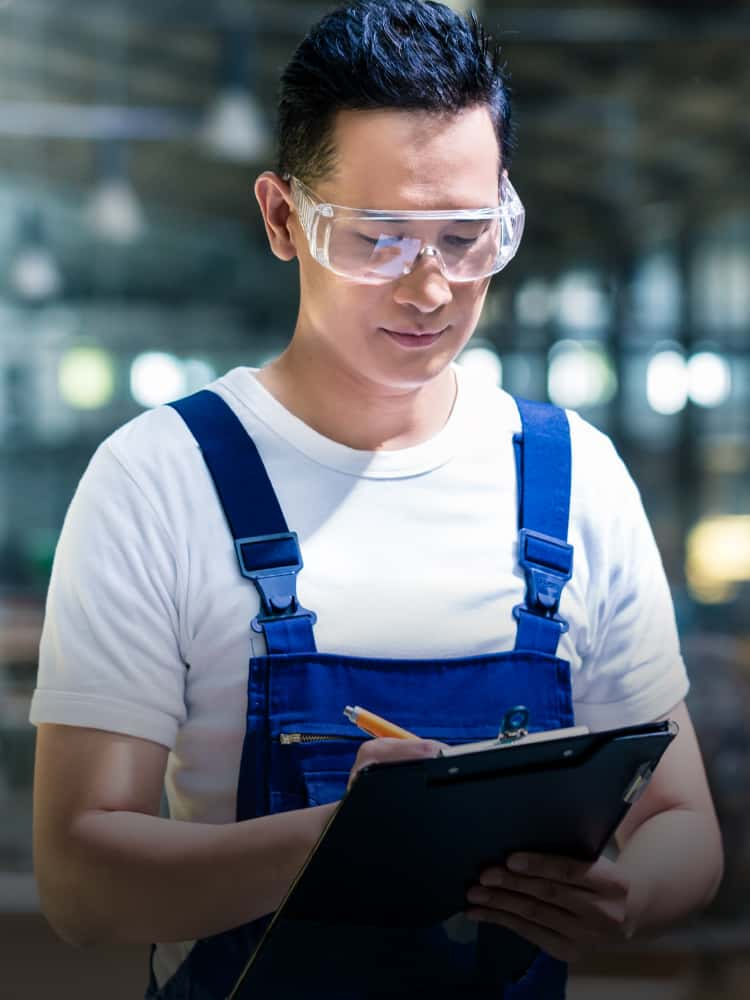 A person wearing safety goggles writing on a clipboard.