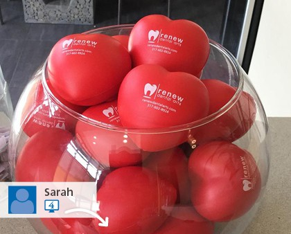 multiple red heart shaped promotional stress balls in a glass bowl.