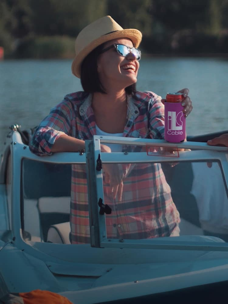 A woman sitting on a boat holding a drink in a promotional can cooler.