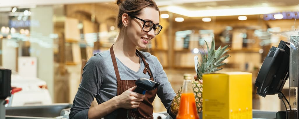 A woman in glasses scanning a pineapple in a store.