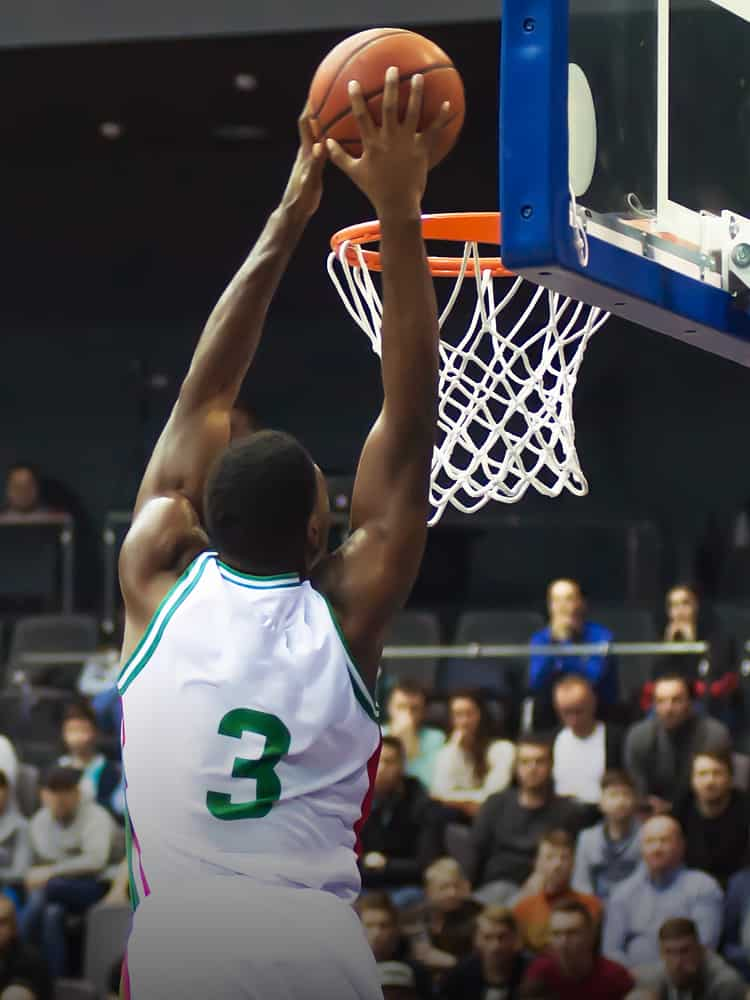 A basketball player performs a slam dunk.