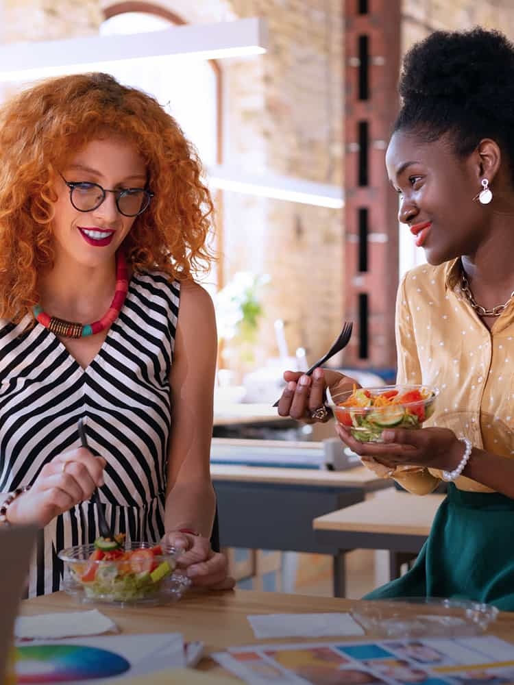 Two women eating a healthy lunch at work
