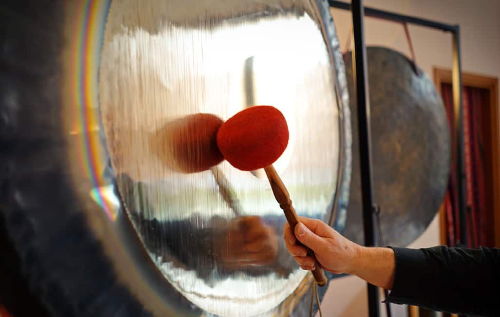 A person striking a gong with a mallet.