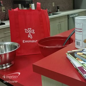 Red canvas bag branded with Emmaus logo and name, sitting on counter with mixing bowls