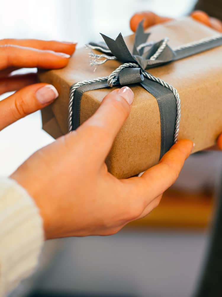 One person hands another a wrapped gift.