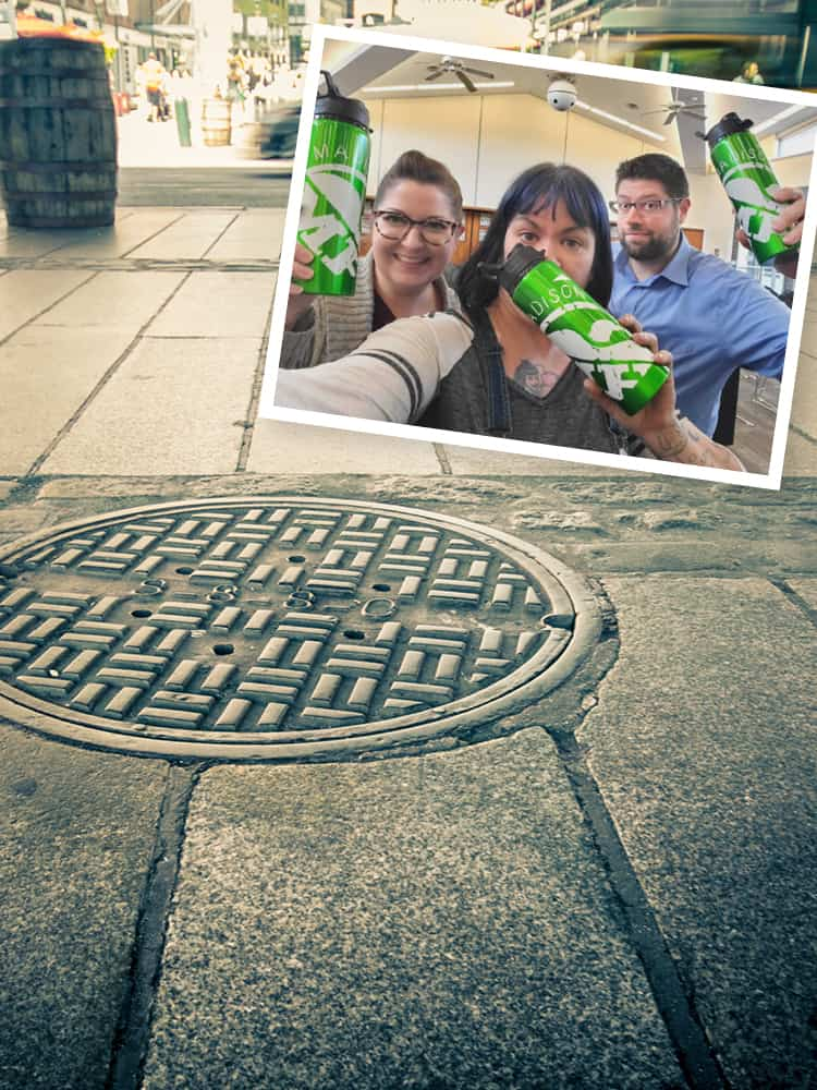 three artists holding promotional water bottles based on the design of a city man-hole cover