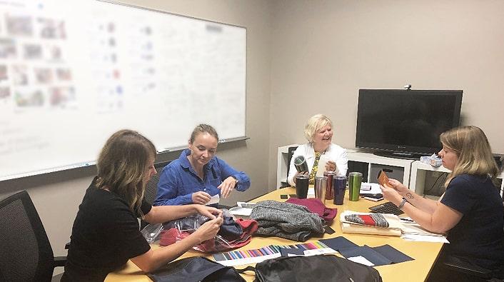 4imprint merchandising team looking over new Crossland promotional fleece line – including drinkware, branded blankets and branded fleece.