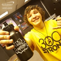 Teenage boy smiling and holding a black plastic water bottle