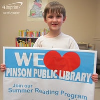 Young boy smiling and holding a library display sign
