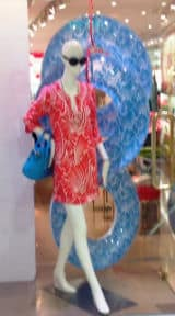 A window display featuring a blue inflatable flip flop as a backdrop.