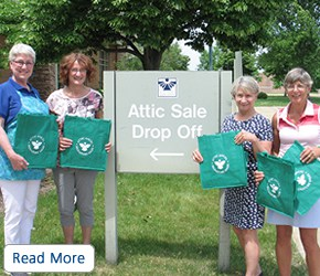 Four women holding green canvas bags by an attic sale drop off sign