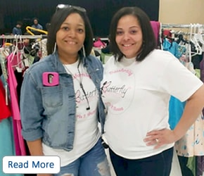 Two women wearing white branded T-shirts in front of clothing racks