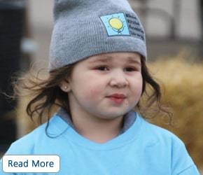 A child wearing a gray branded hat and blue T-shirt