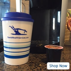 White and blue tumbler in front of a Keurig coffee machine with coffee pod