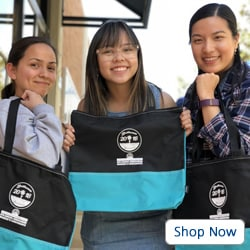 Three women smiling and holding black and teal swag bags