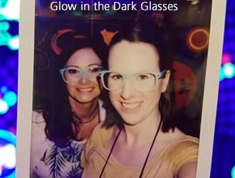 Two girls wearing glow in the dark glasses