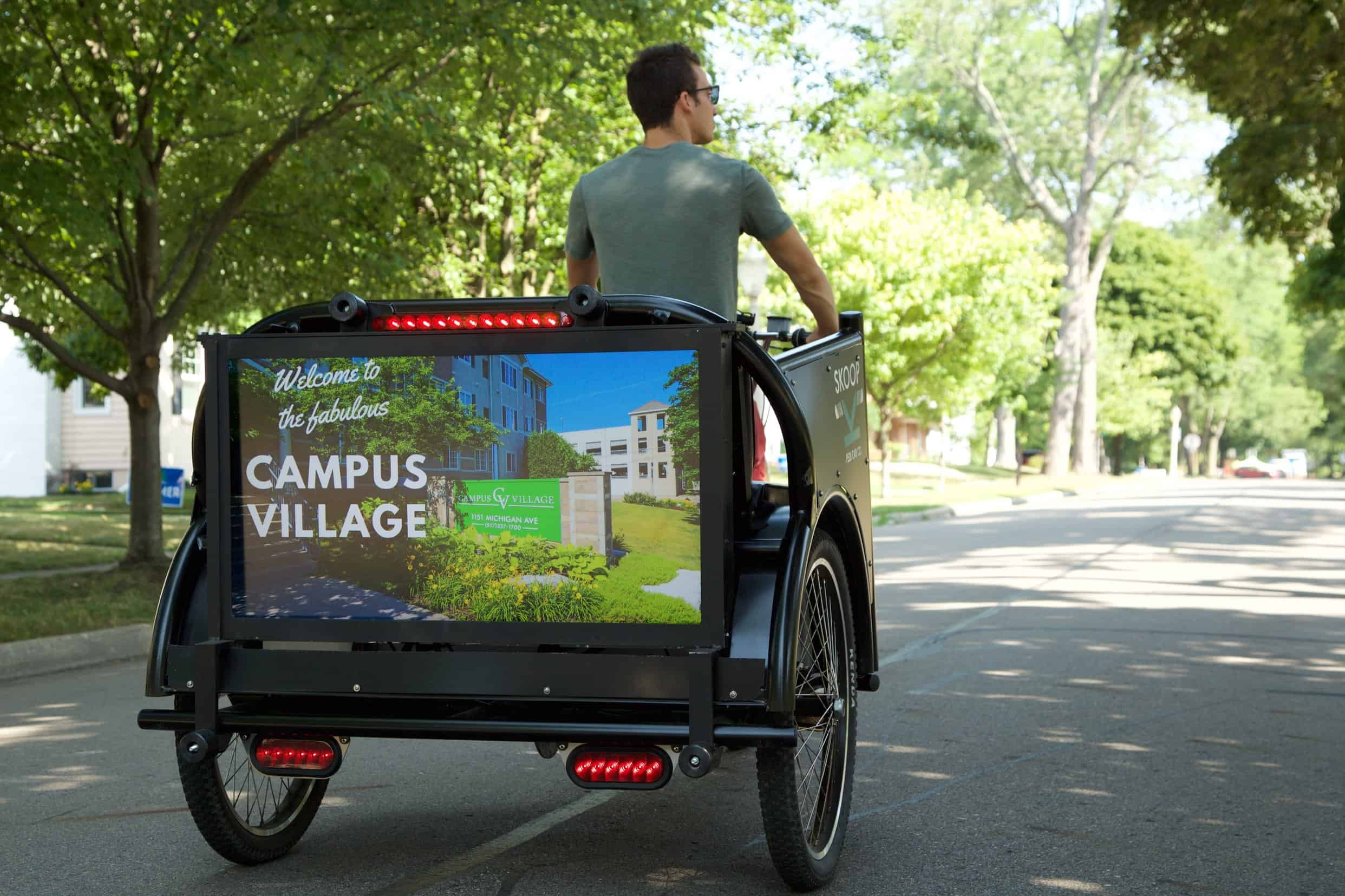 Man driving rickshaw on college campus with advertisement attached on back