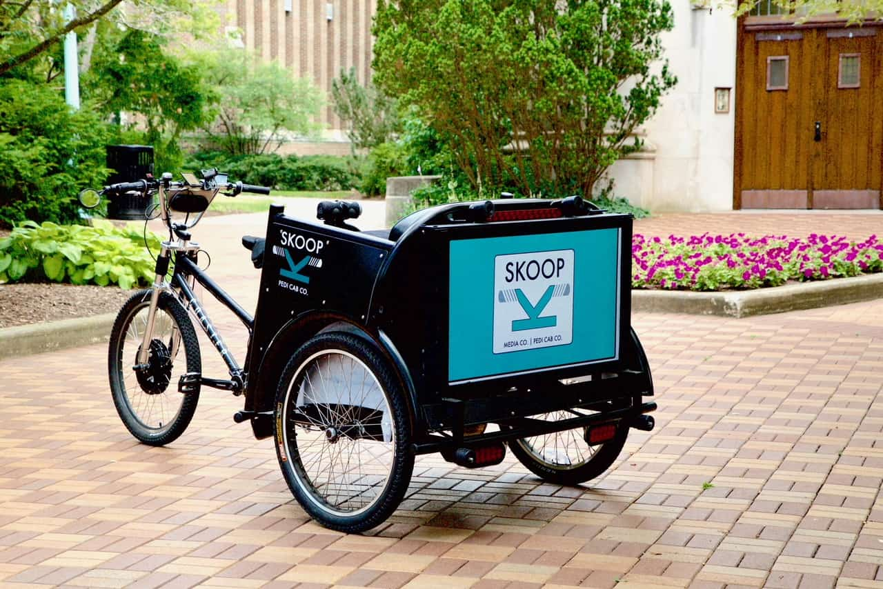 Bicycle-driven rickshaw on college campus with advertisement on back